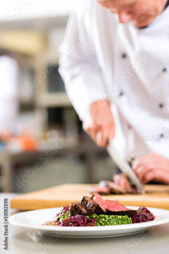 Chef in restaurant kitchen preparing food