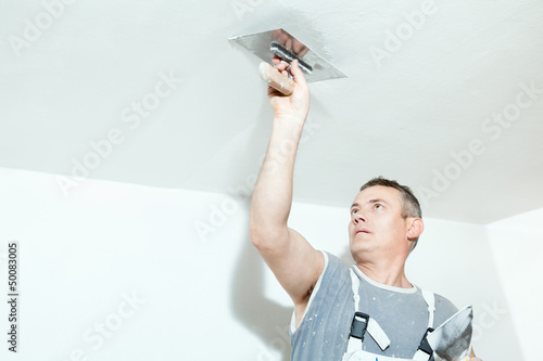 Plasterer spreading out plaster with trowel over the ceiling