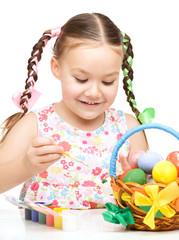 Little girl is painting eggs preparing for Easter
