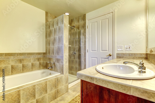 Bathroom with tub,  small shower and wood cabinets.