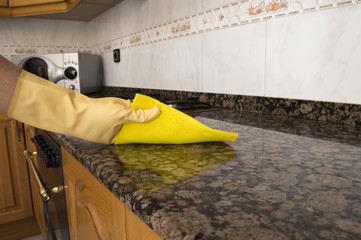Woman cleaning kitchen with yellow cloth
