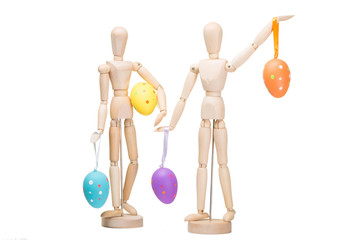 Two wooden little men with easter eggs on isolated white