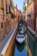 A channel in Venice at the sundown with boats parked around