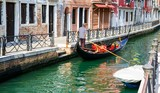 Gondolier paddling his gondola through a small channel in Venice