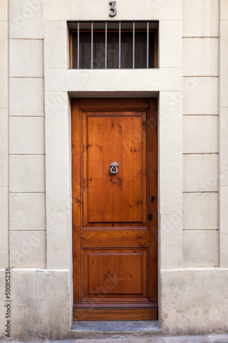 Single wooden door with knocker on Sarrià quarter (Barcelona)