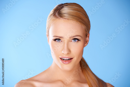 Close up portrait of blond woman on blue