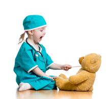 Adorable dziecko ubrane jak lekarz gry z zabawki nad białym