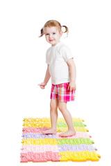 little girl massaging her feet on carpet