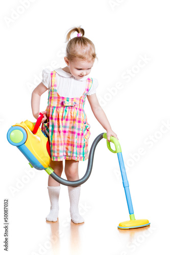 kid girl playing and cleaning room with toy vacuum cleaner