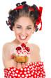 Hübsche Frau im Pin Up Style lacht mit Cupcake