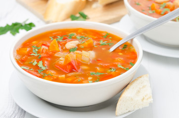 Vegetable soup with white beans in a bowl and spoon horizontal