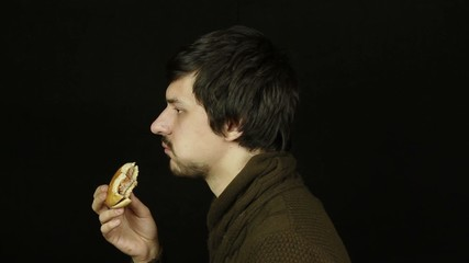 Man eating a hamburger on a black background