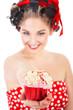 Junge sexy Frau in  Pin Up Style überreicht lachend Cupcake