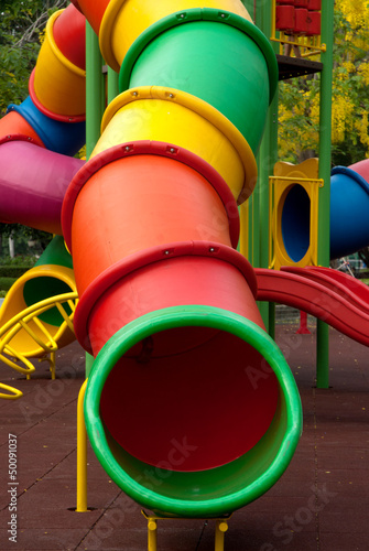 Colorful spiral tube slide at public playground .