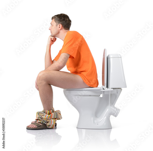 Thoughtful man sitting on the toilet, white background