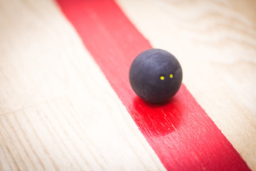 Squash ball on red line