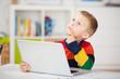 nachdenklicher kleiner junge am computer