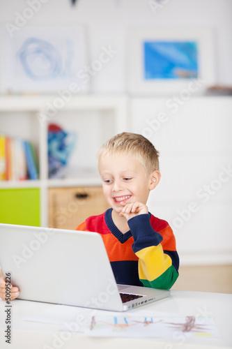 kleiner junge hat spaß am computer