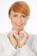 Beautiful smart woman showing symbol of heart with fingers