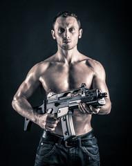 Confident young man shirtless portrait with machine gun