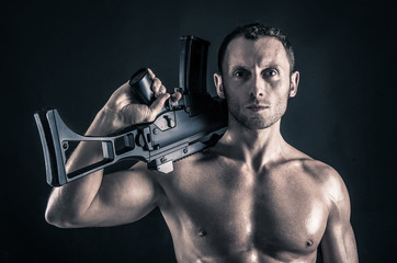 Confident young man shirtless portrait with machine gun