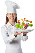 Happy cook woman holding a dish with floating vegetables