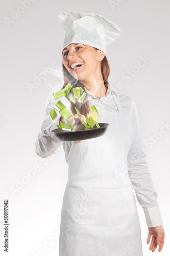 Happy cook woman holding a pan with creative cuisine