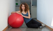 Portrait of young woman with ball in the gym.