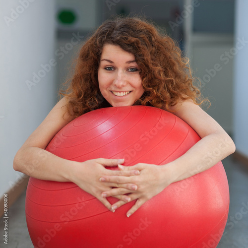 Funny portrait of young woman with ball in the gym.