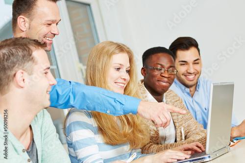 Lehrer zeigt auf Computer im Unterricht