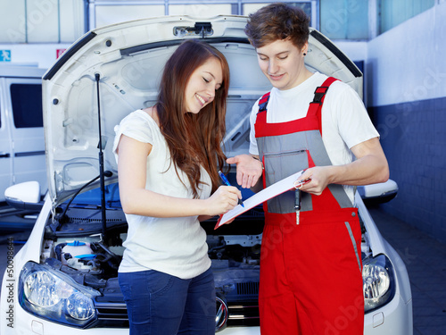 Car mechanic and female customer look at the repair costs