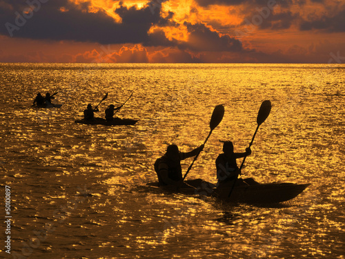 Silhouette of kayakers at sunset