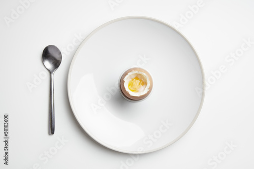 Boiled egg on plate with spoon
