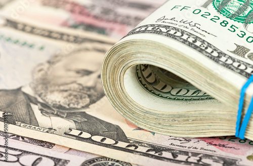 Folded dollar bills wrapped by rubber on money background