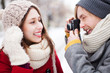 Young man taking photo of woman in winter