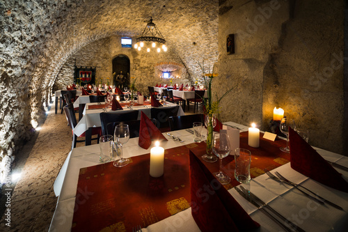 romantic arch stonewall in knight room with tables and candlelit - 50106096