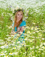 happy young woman in a wreath from wild flowers in field
