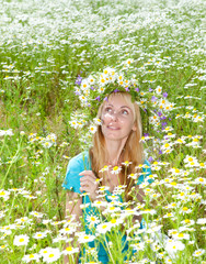 woman in a wreath from wild flowers in the chamomile field