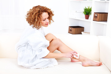 Beautiful woman shaving her legs with epilator