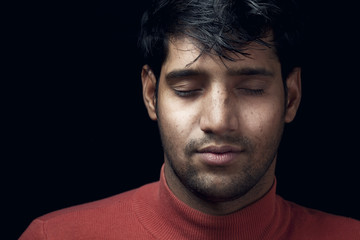 Portrait of young Indian man closed eyes over dark