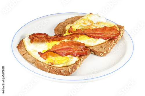 Two brown bread with fried egg and bacon.