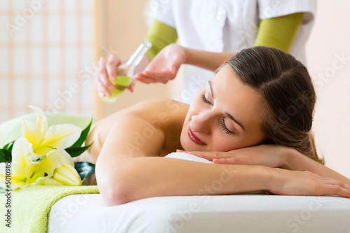 woman having wellness back massage in spa