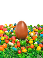 Easter chocolate egg and caramels on the green grass