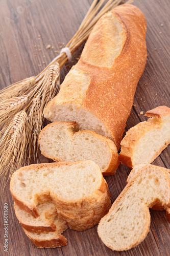 baguette and sliced on wood background