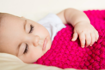 Sleeping baby covered with knitted blanket
