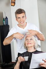 Hairstylist Cutting Woman's Hair In Salon