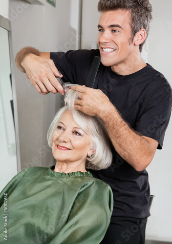 Hairstylist Cutting Client's Hair In Parlor