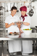 Chefs Using Digital Tablet In Kitchen