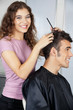 Happy Female Hairdresser Cutting Client's Hair