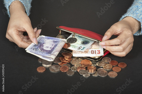 Woman's hands with Stirling currency and a red purse